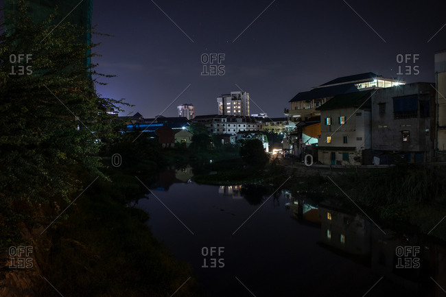 Buildings reflected in water in the dark of night