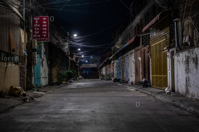 Phnom Penh, Cambodia - December 3, 2018: Locked gates and doors to closed businesses along an empty street at night