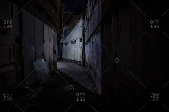 Phnom Penh, Cambodia - December 4, 2018: Dark narrow alley between buildings at night