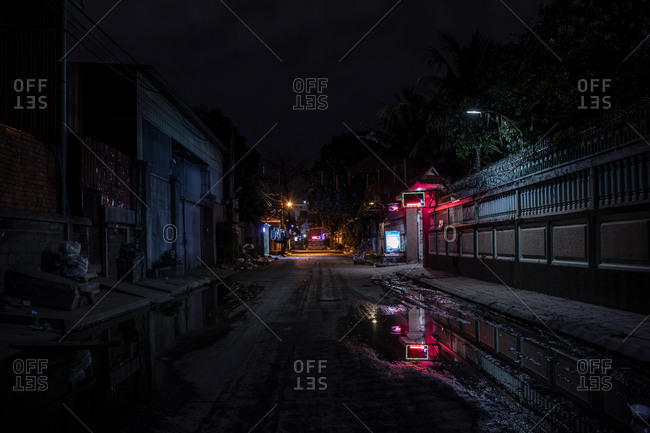 Phnom Penh, Cambodia - December 3, 2018: Neon lights from a business reflected in a puddle on the street in the dark of night