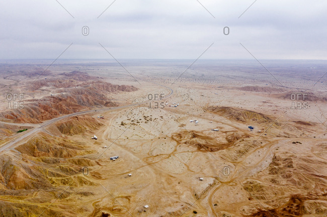 Desert in California with vehicles parked at a cliff, seen from the sky.