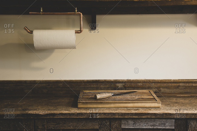 High angle view of wooden chopping board and knife on vintage wooden kitchen cupboard.