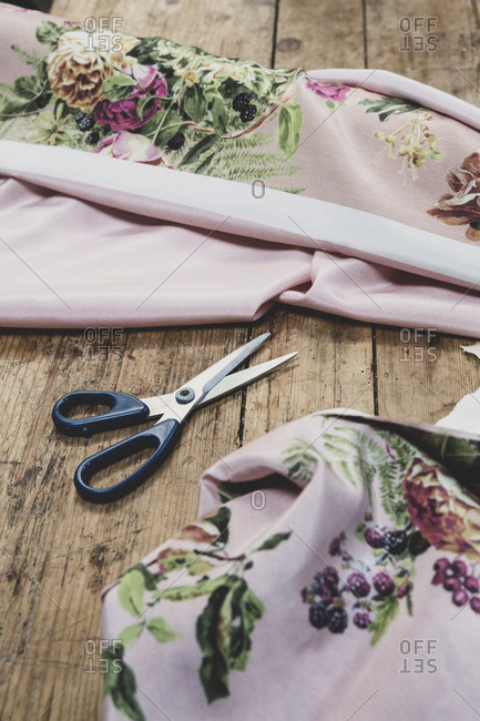 High angle close up of pair of scissors and pink fabric with floral pattern on wooden table.
