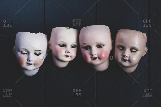Close up of four porcelain dolls' heads on black background.