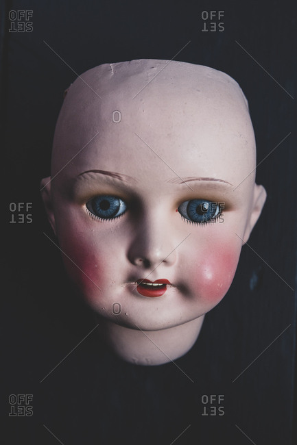 Close up of four porcelain doll's head on black background.