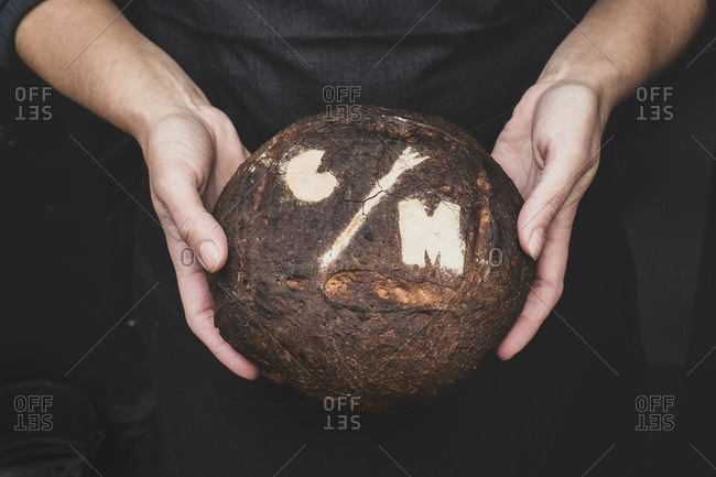 High angle close up of human hands holding freshly baked loaf of bread.