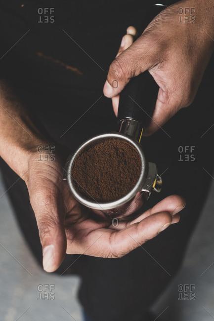 High angle close up of person holding espresso machine portafilter with ground espresso.