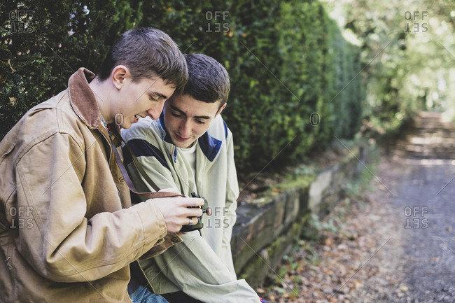 Young man and teenage boy with short brown hair wearing casual jackets sitting on hedged stone wall, looking at image on digital camera.