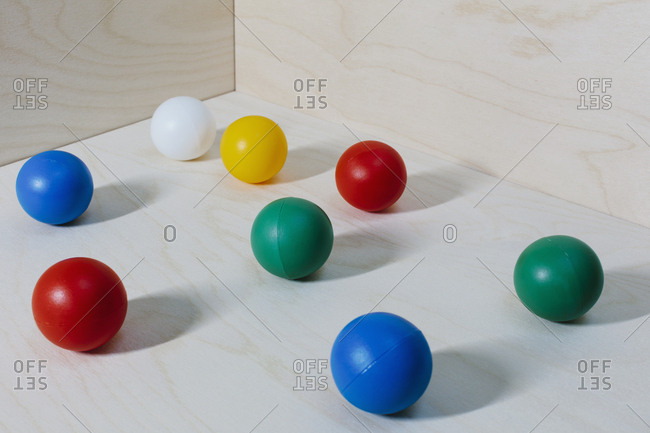 Multicoloured balls arranged on wood background, close up