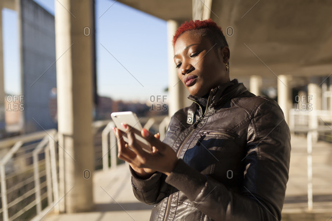 Beautiful and afro woman communicating with her smart phone