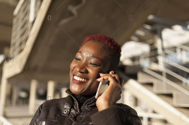 Beautiful and afro woman communicating with her smart phone and smiling