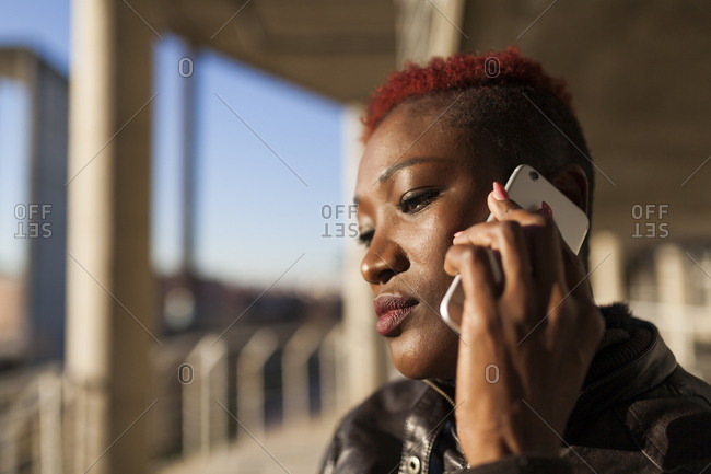 Beautiful and afro woman communicating with her smart phone and serious face