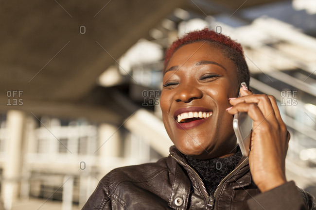 Beautiful and afro woman communicating with her smart phone and laughing