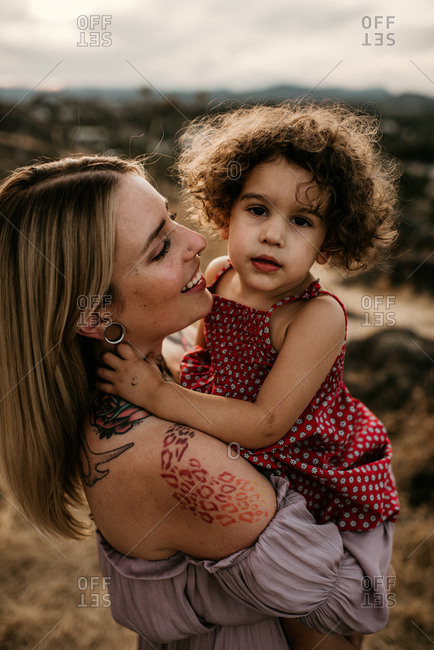 Mother with tattoos and stretched ears holding daughter in nature