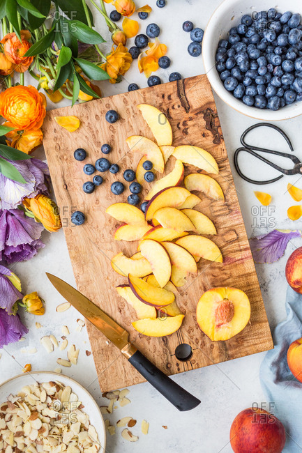 Blueberries and peaches on a cutting board by almonds and flowers