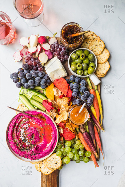 Cheeseboard filled with fruit, cheese, crackers, olives, figs, nuts, and served with wine