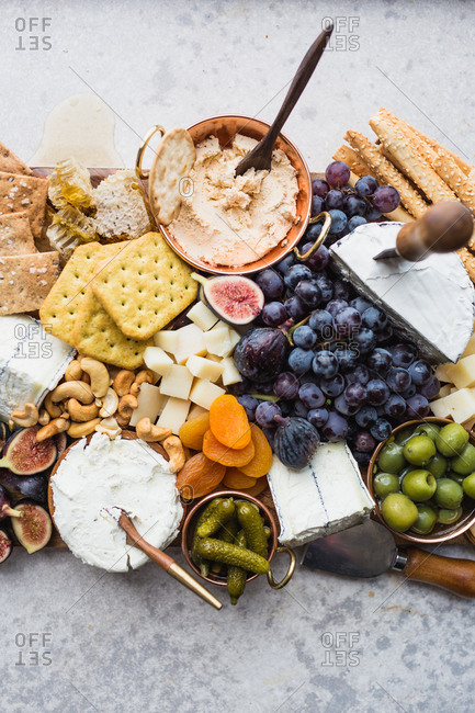 Cheeseboard with fruit, cheese, crackers, olives, figs, and nuts on blue background