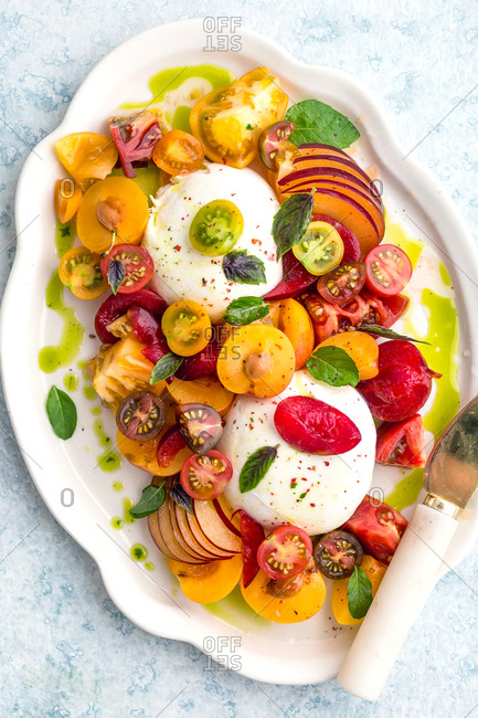 Burrata peaches heirloom tomatoes and basil on a serving platter