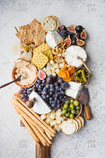 Cheeseboard with fruit, cheese, crackers, olives, figs, and nuts on light background