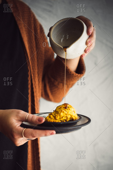 Woman pouring maple syrup over a drop biscuit