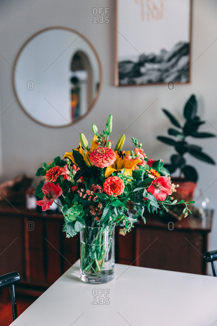 Flowers in vase on dining room table with mirror and plants in background