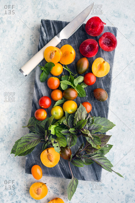 Tomatoes and plum ingredients on cutting board