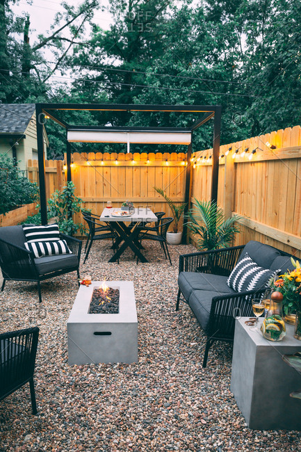 Backyard set up for entertaining with rocks couches and tables