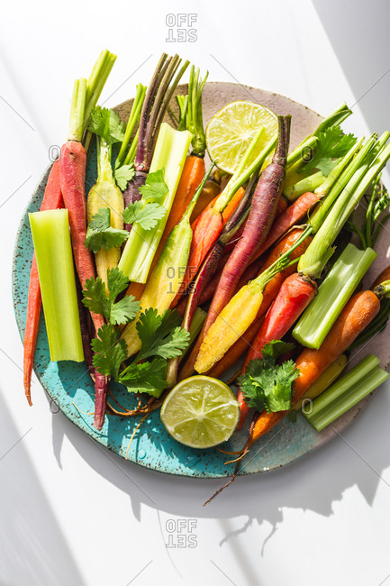 Carrots celery lime ingredients for carrot soup on blue and pink background