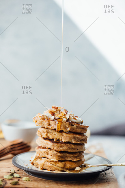 Stack of pancakes with maple syrup pouring on them