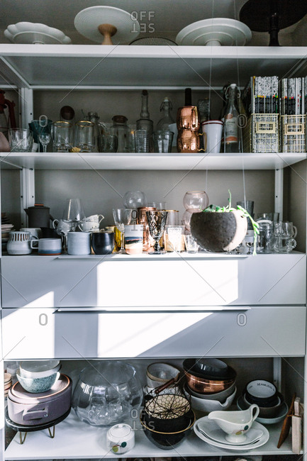 Ceramics and kitchen items on shelves with light reflecting