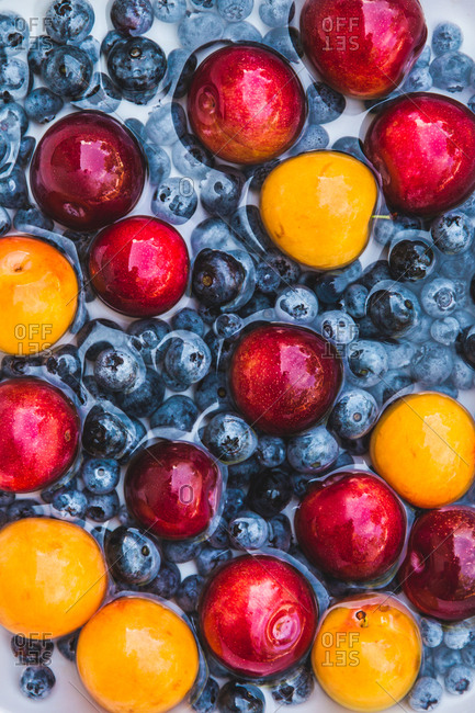 Blueberries and stone fruit being washed off before prepping