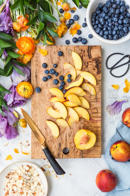 Blueberries and peaches being cut on a cutting board by almonds and flowers
