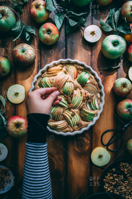Hand sprinkling brown sugar over apple cake with wood background