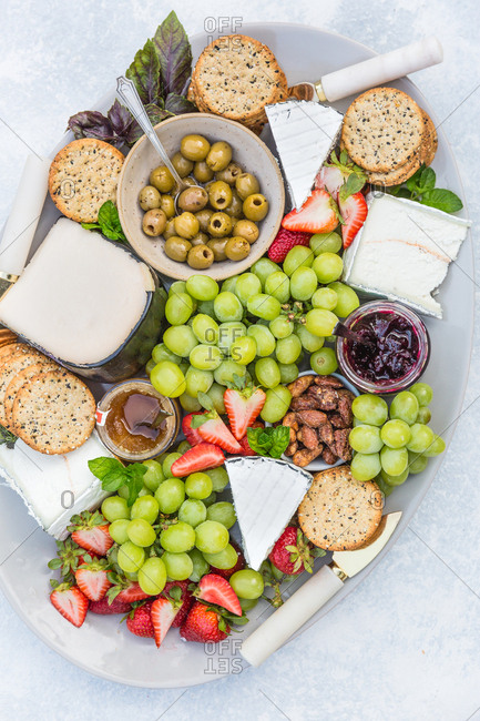 Cheeseboard and fruit plate with crackers grapes nuts olives and jam