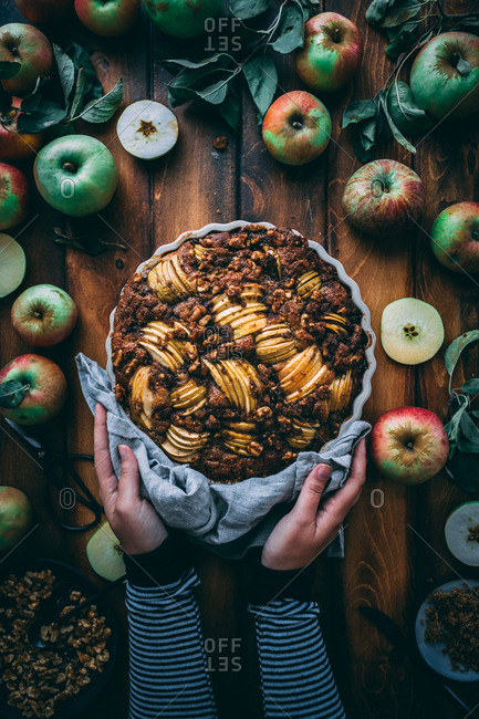 Hands holding apple cake with wood background