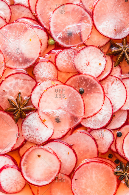 Close-up of sliced radishes being pickled with star anise and black pepper