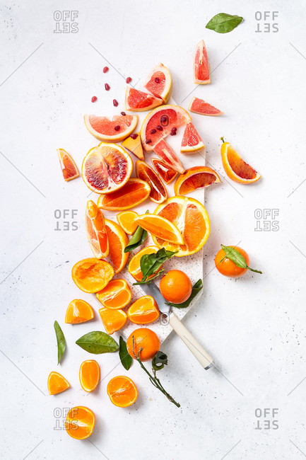 Citrus fruit cut on cutting board with white marble background