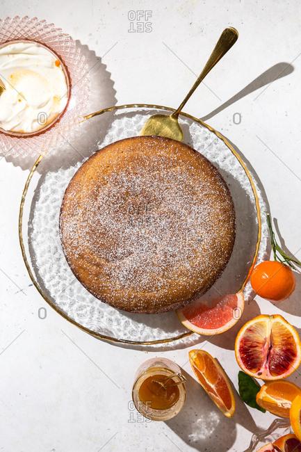Whole citrus homemade cake on white background with blood oranges and yogurt
