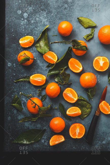 Clementines with leaves scattered on dark blue background