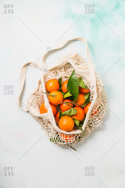 Fresh clementine oranges in produce bag on blue marble background