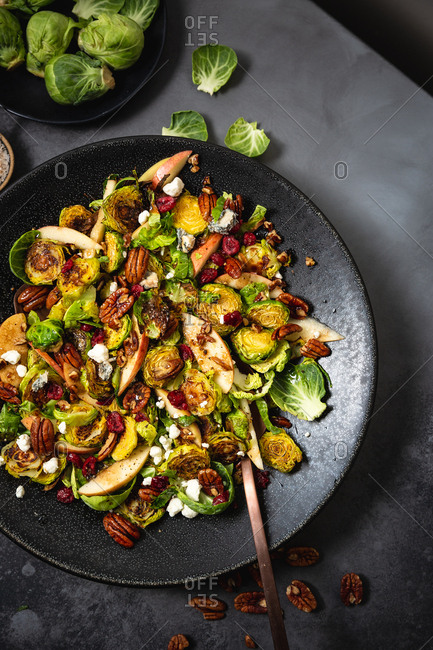 Brussel sprout salad in big black bowl on grey background