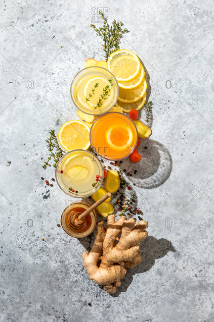Lemon ginger and orange drinks with honey and whole ginger on grey speckled background