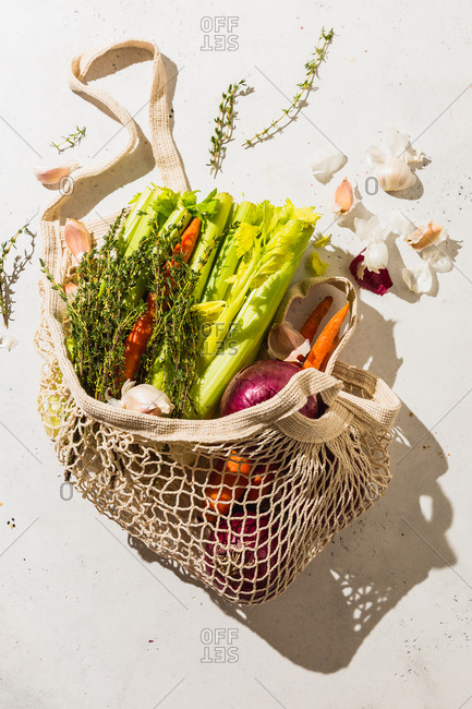 Vegetable and herbs in grocery bag on white background