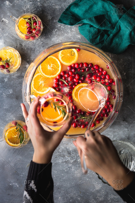Hands pouring a glass of cranberry and orange holiday punch