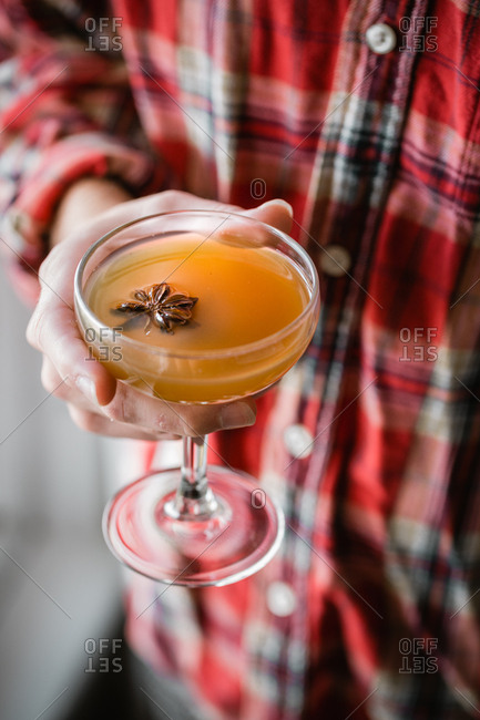 Apple cider cocktail with star anise in hand