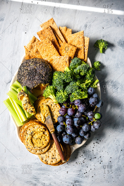 Cheese ball on serving plate with crackers, vegetables, and fruit