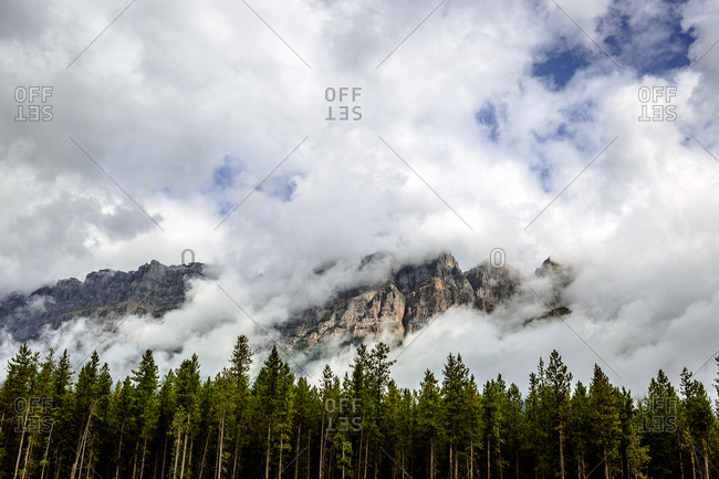 Mountains covered in clouds with trees in Banff Canada