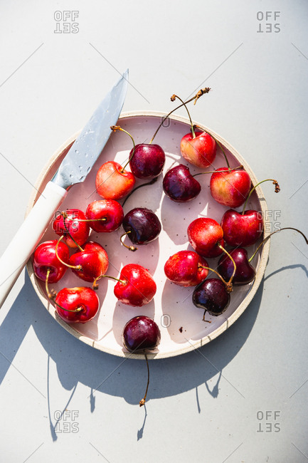 Cherries on pink plate with knife in bright summer