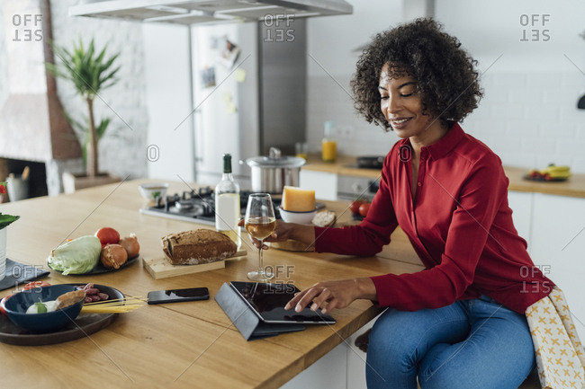 Woman sitting in kitchen with a glass of white wine- using digital tablet