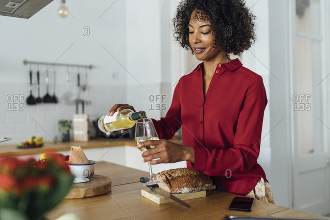 Woman standing in kitchen- pouring herself a glass of white wine